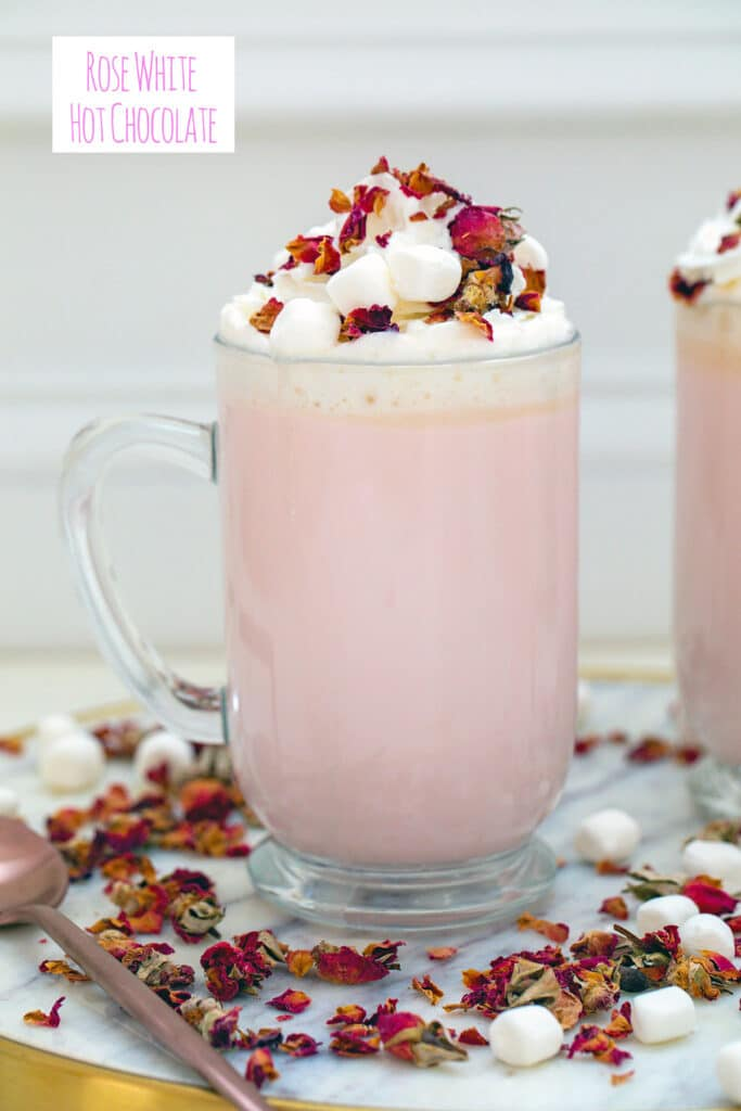 Head-on view of a big mug of pink colored rose white hot chocolate topped with whipped cream, mini marshmallows, and rose petals with rose petals all around and recipe title at top