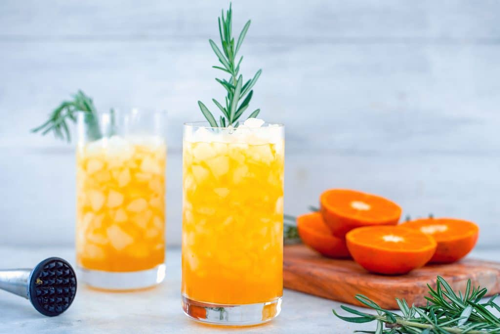 Landscape view of two tall glasses of tangerine and rosemary cocktail with rosemary garnish with cutting board with tangerines and rosemary and muddler in the background