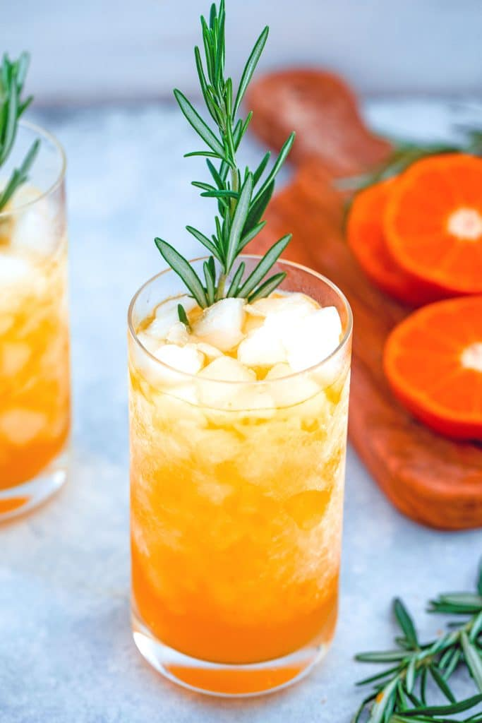 Close-up image of tangerine and rosemary cocktail in a tall glass with crushed ice and rosemary garnish with cutting board with tangerines and rosemary in the background