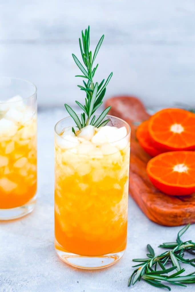 Head-on view of tangerine and rosemary cocktail in a tall glass with rosemary garnish and second cocktail, cutting board with sliced tangerines and rosemary in the background