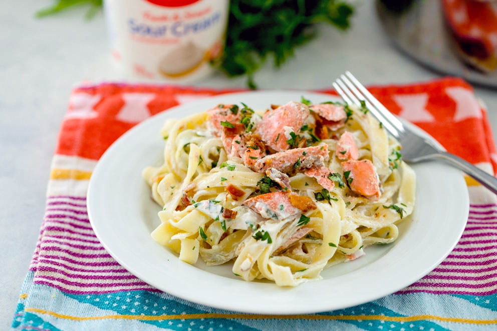 Landscape photo of white plate with cream-covered fettuccine with salmon, bacon, and herbs with fork on the plate and sour cream container and parsley in the background