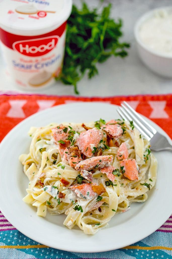 Creamy fettuccine on a white plate with salmon, bacon, and herbs and sour cream container and parsley in the background