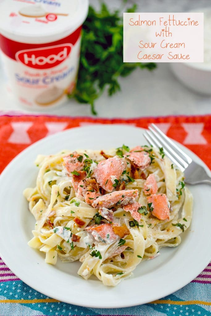 "Creamy fettuccine on a white plate with salmon, bacon, and herbs and sour cream container and parsley in the background with ""Salmon Fettuccine with Sour Cream Caesar Sauce"" text at the top"