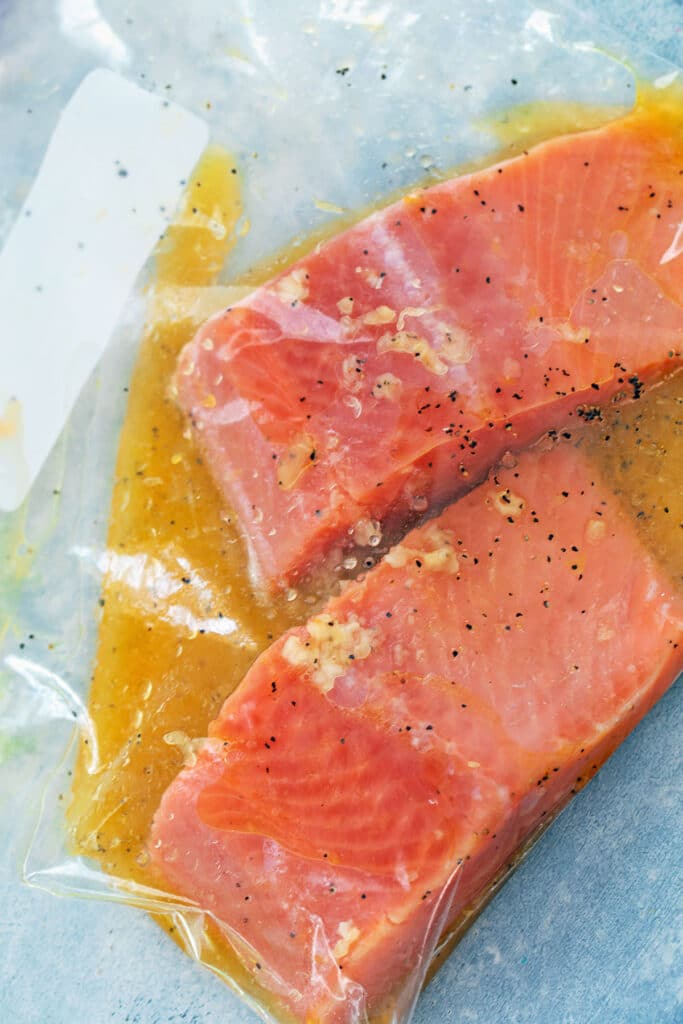 Salmon marinating in citrus dressing in plastic bag