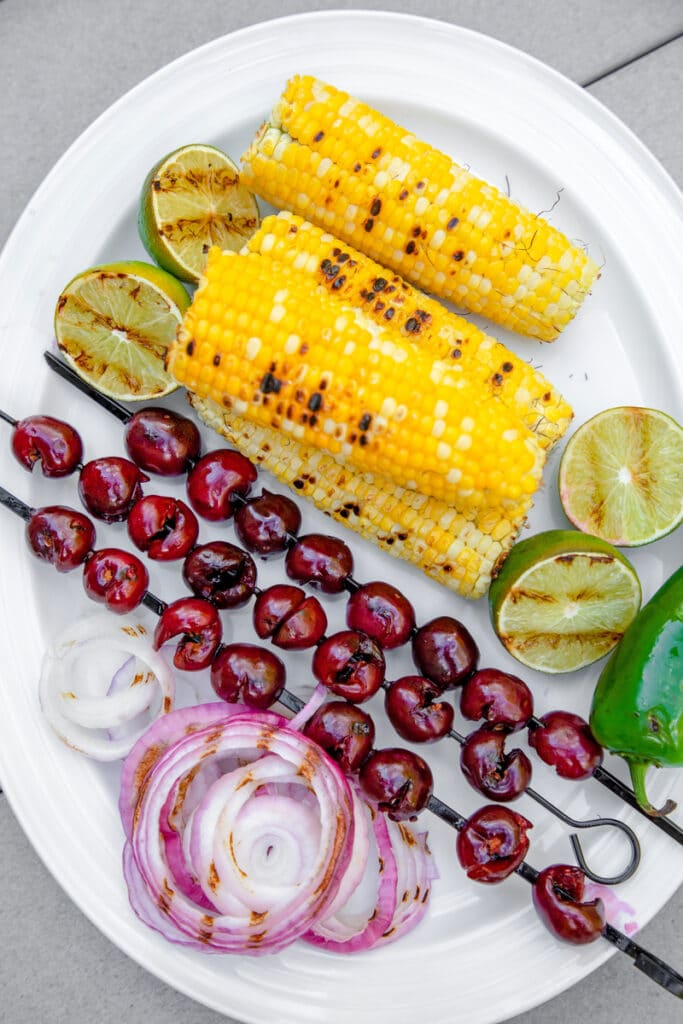 Overhead view of white platter with grilled cherries on skewers, corn on the cob, lime halves, jalapeño, and red onion