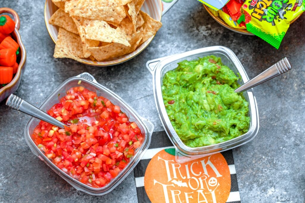 containers of salsa and guacamole with tortilla chips in background