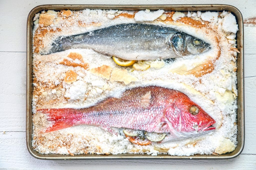 Landscape view of a whole branzino and whole red snapper stuffed with herbs and citrus on a baking sheet with salt chipped away