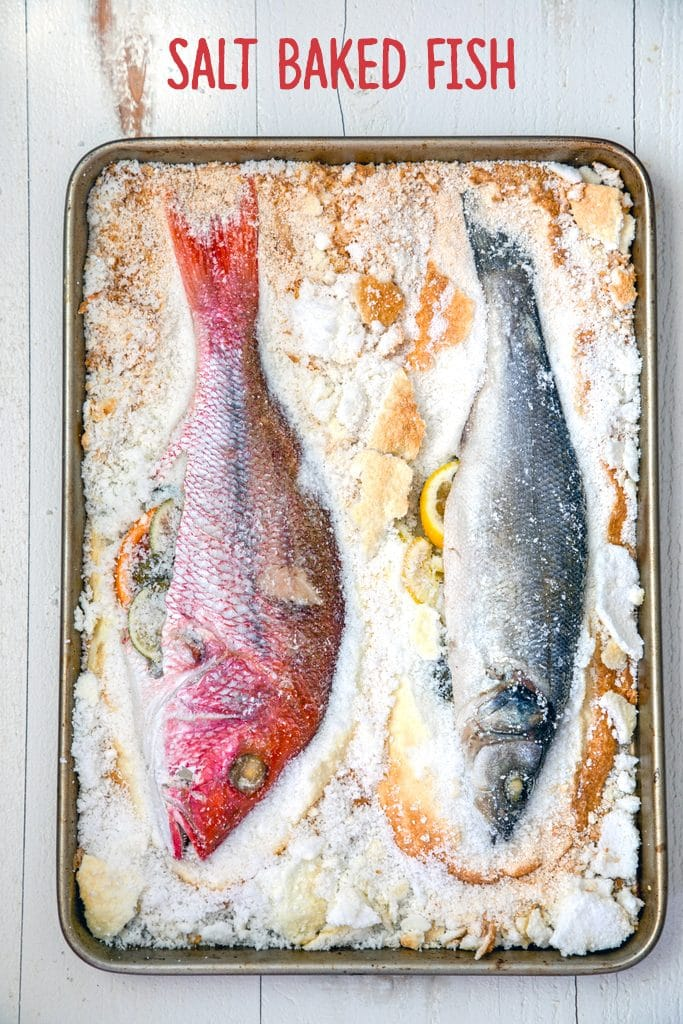 "Overhead view of two fish whole on a baking pan with salt chipped away and ""salt baked fish"" text at the top"