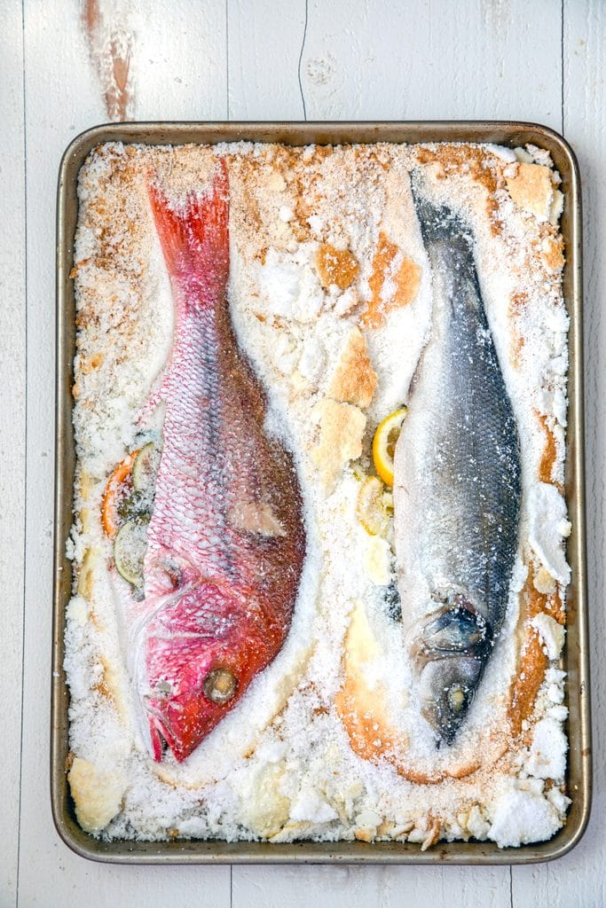 Overhead view of two fish whole on a baking pan with salt chipped away