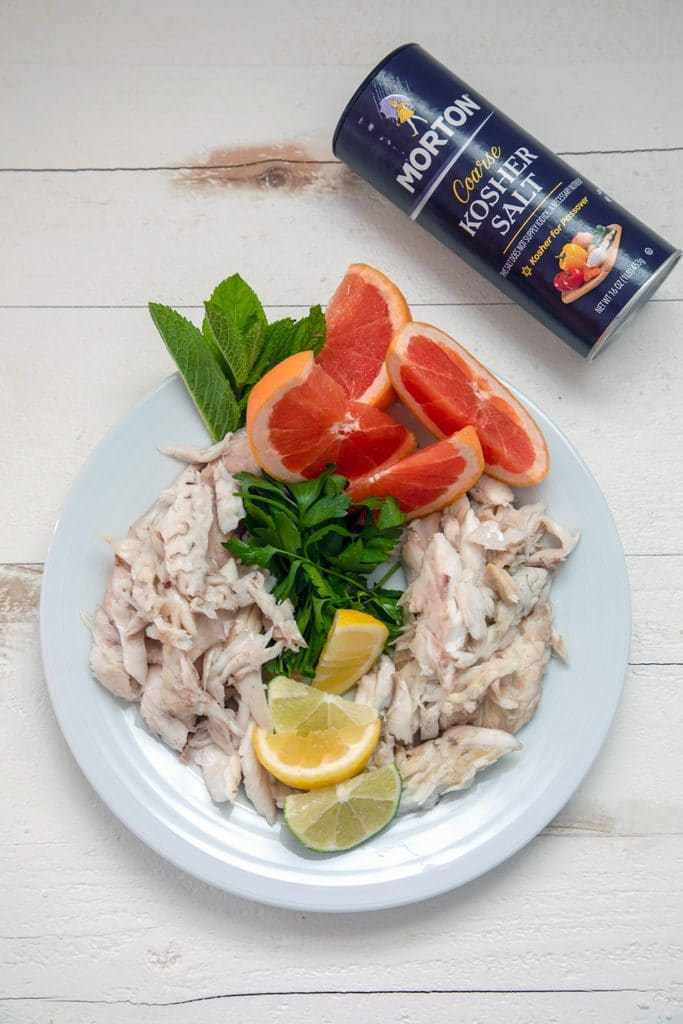A white plate with fish cut up, lemons, grapefruit, and herbs and a container of Morton salt on the side