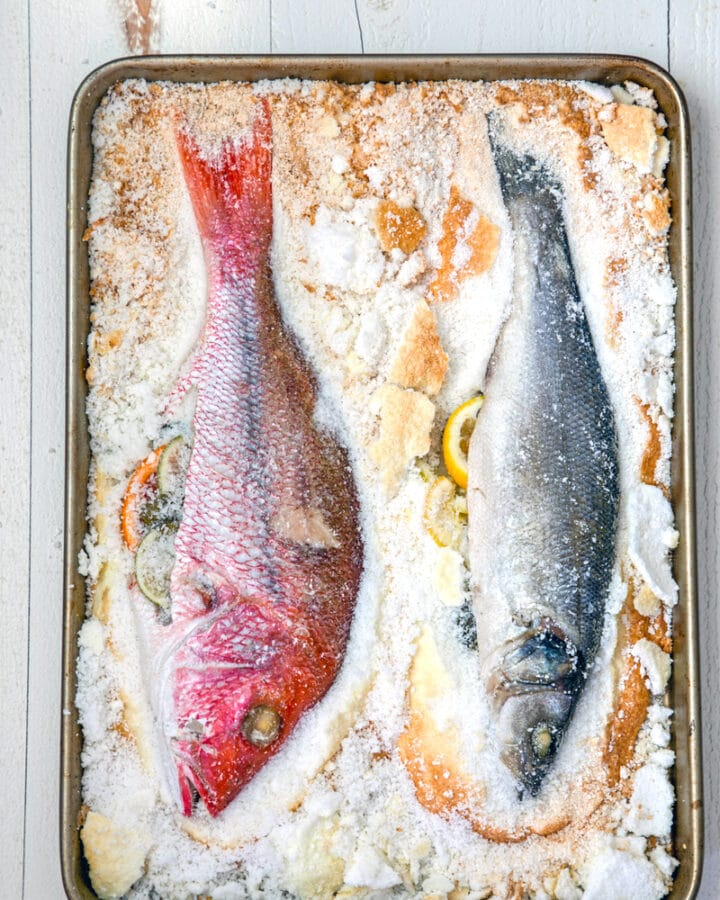 Overhead view of salt baked fish with two whole fishes on a baking sheet surrounded by salt