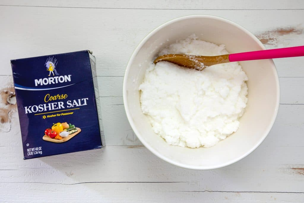Overhead view of box of Morton kosher salt and big bowl filled with salt and egg white mixture with wooden spoon