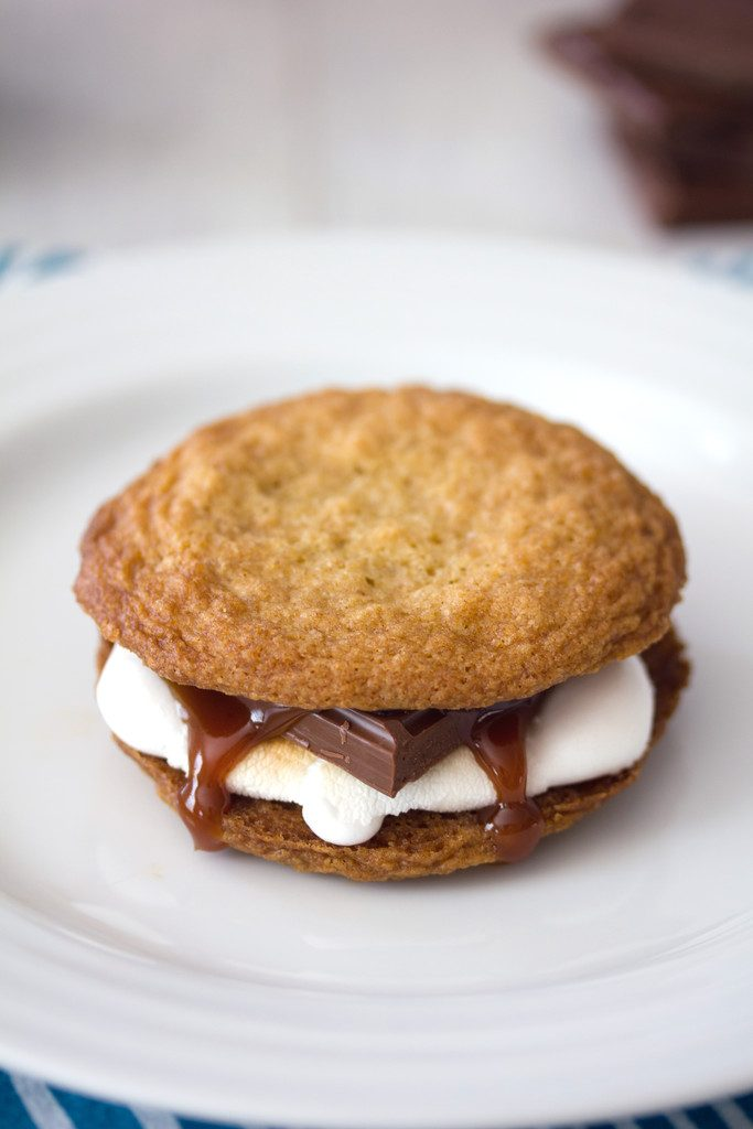 Head-on view of a salted caramel cookie s'mores on a white plate with melted marshmallow, chocolate, and salted caramel oozing out the sides
