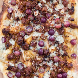 Sausage, Grape, and Gorgonzola Flatbread Pizza -- A seemingly unlikely combination, the flavors in this flatbread pizza work so well together, you'll find yourself craving this ultra thin crust pizza all the time | wearenotmartha.com #flatbread #pizza #sausage #gorgonzola #appetizer