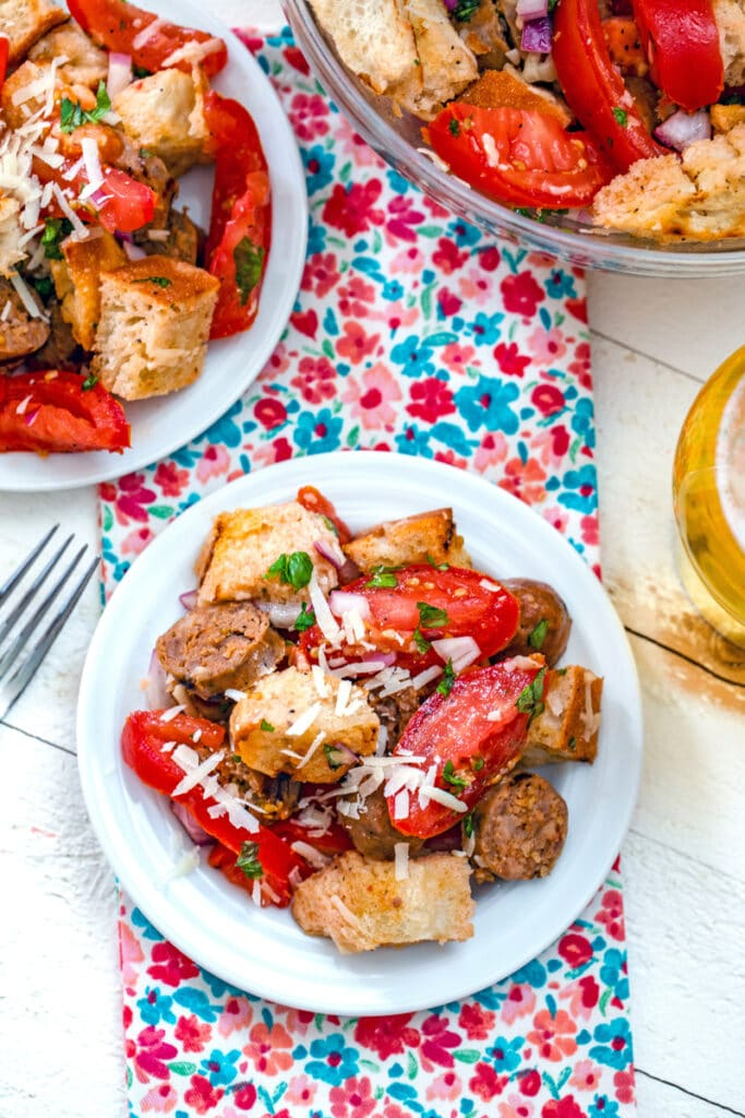 Overhead view of sausage panzanella with tomatoes, basil, bread, and parmesan on a plate with another plate and bowl in background