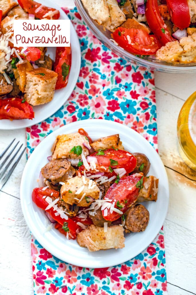 Overhead view of sausage panzanella with tomatoes, basil, bread, and parmesan on a plate with another plate and bowl in background and recipe title at top