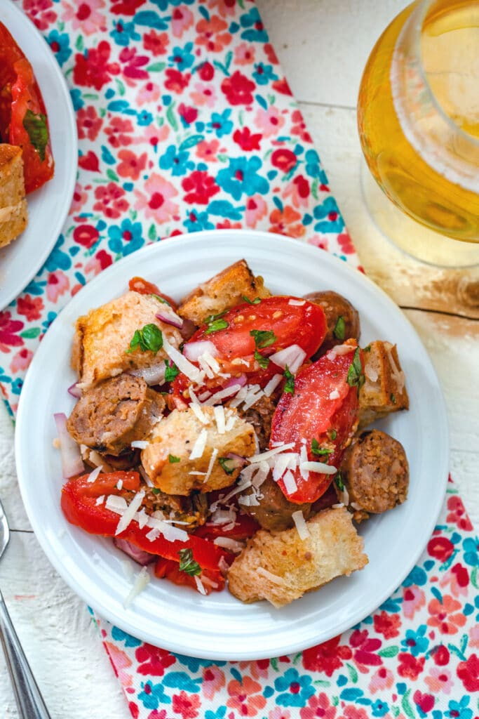 View of sausage panzanella with tomatoes, basil, bread, and parmesan on a plate