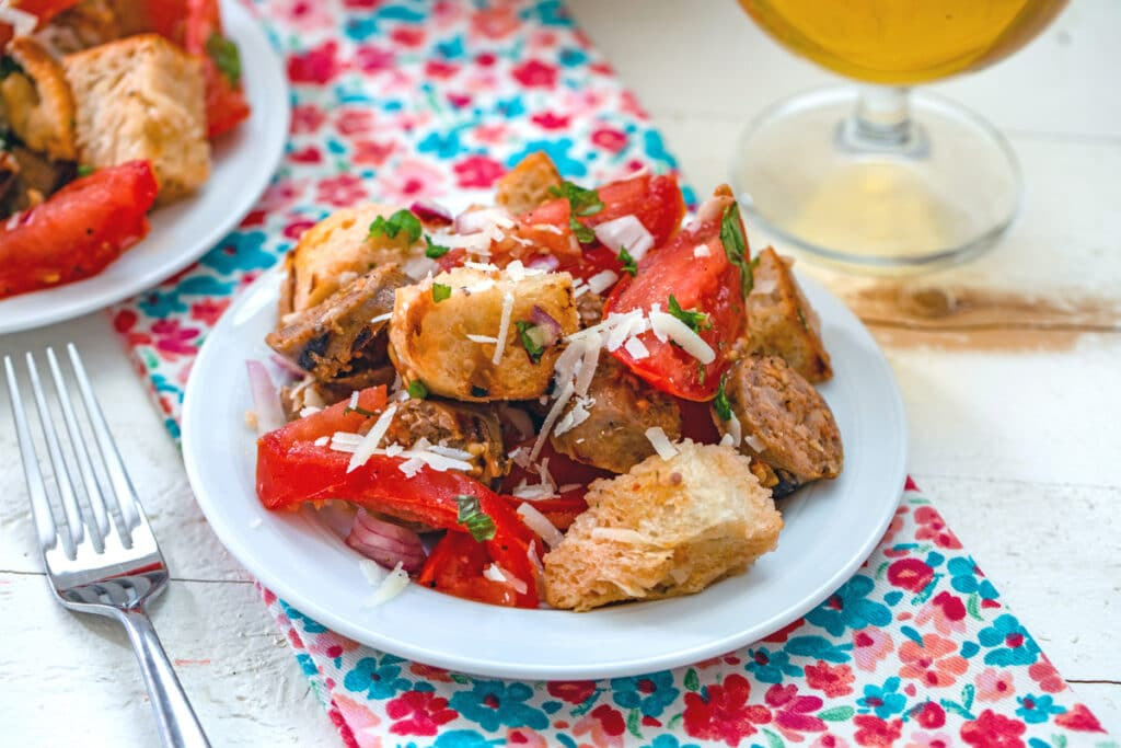 Lanscape head-on view of sausage panzanella salad on a plate with second plate and glass of beer in the background