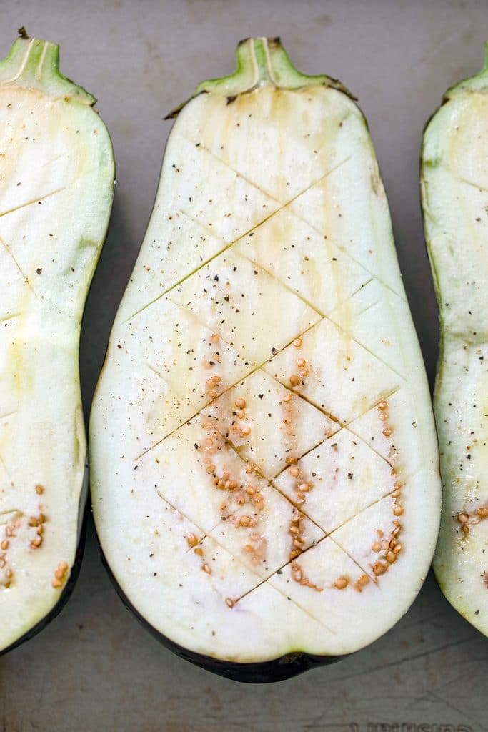 Overhead view of scored eggplant halves with zigzag cuts in them and salt and pepper