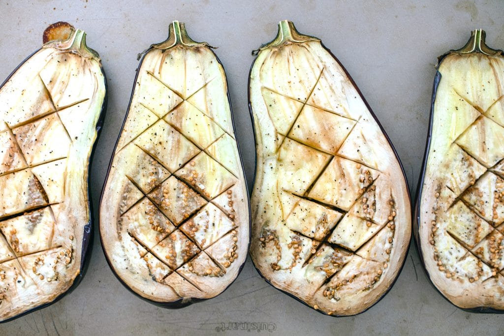 Overhead view of four eggplant halves scored with zigzag cuts after being baked