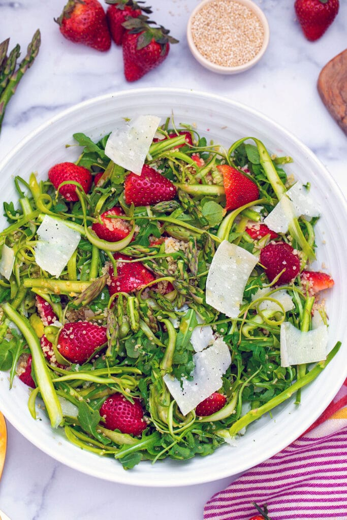 Overhead view of white serving bowl with shaved asparagus salad with arugula, strawberries, quinoa, and parmesan shavings with strawberries, asparagus, quinoa, and dressing jar in background