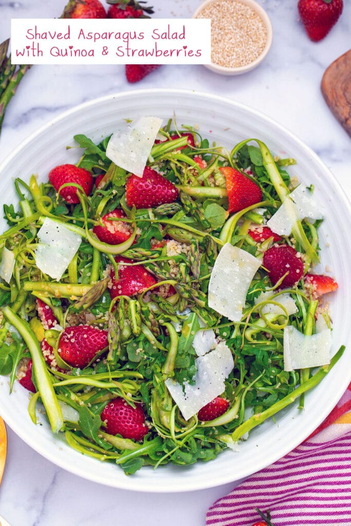 Overhead view of white serving bowl with shaved asparagus, arugula, strawberries, quinoa, and parmesan shavings with recipe title at top