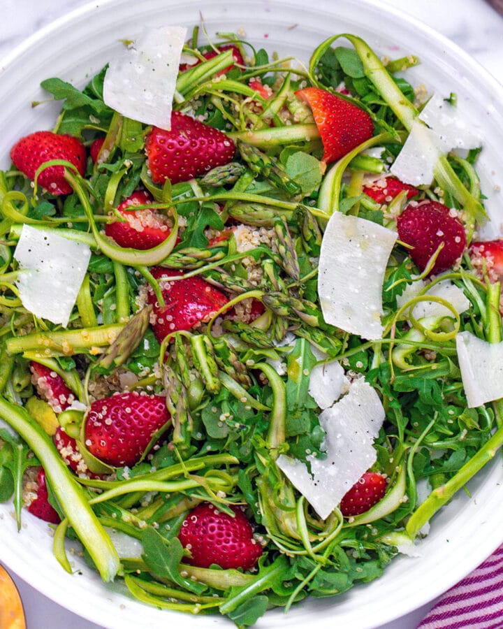 Overhead closeup view of white salad bowl with shaved asparagus, arugula, strawberries, quinoa, and parmesan shavings