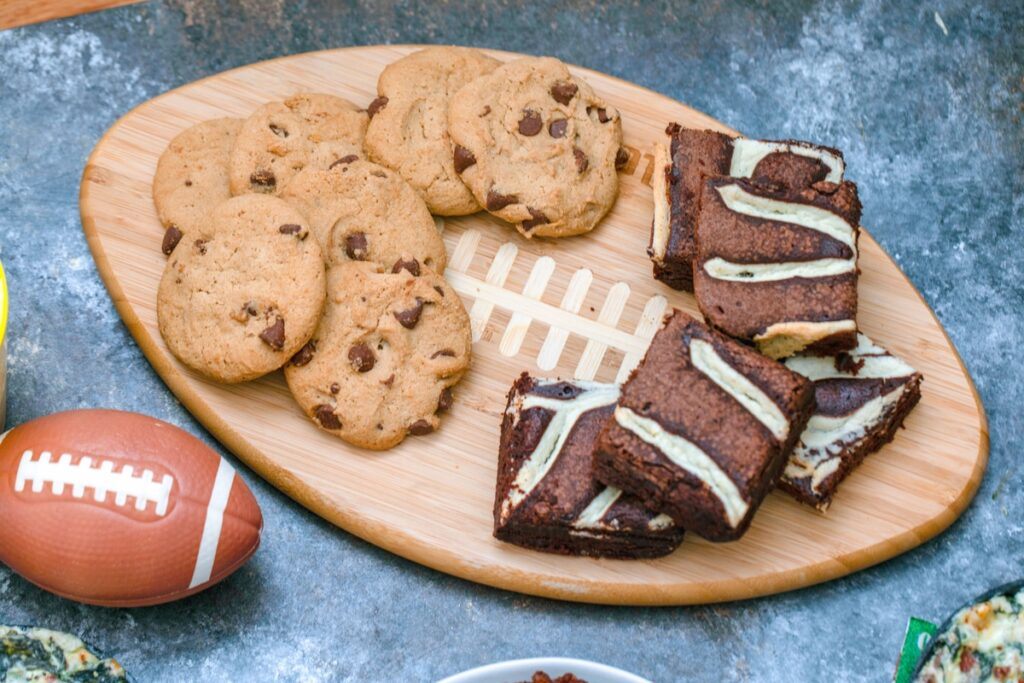 Chocolate chip cookies and brownies on football shaped board with mini football in background
