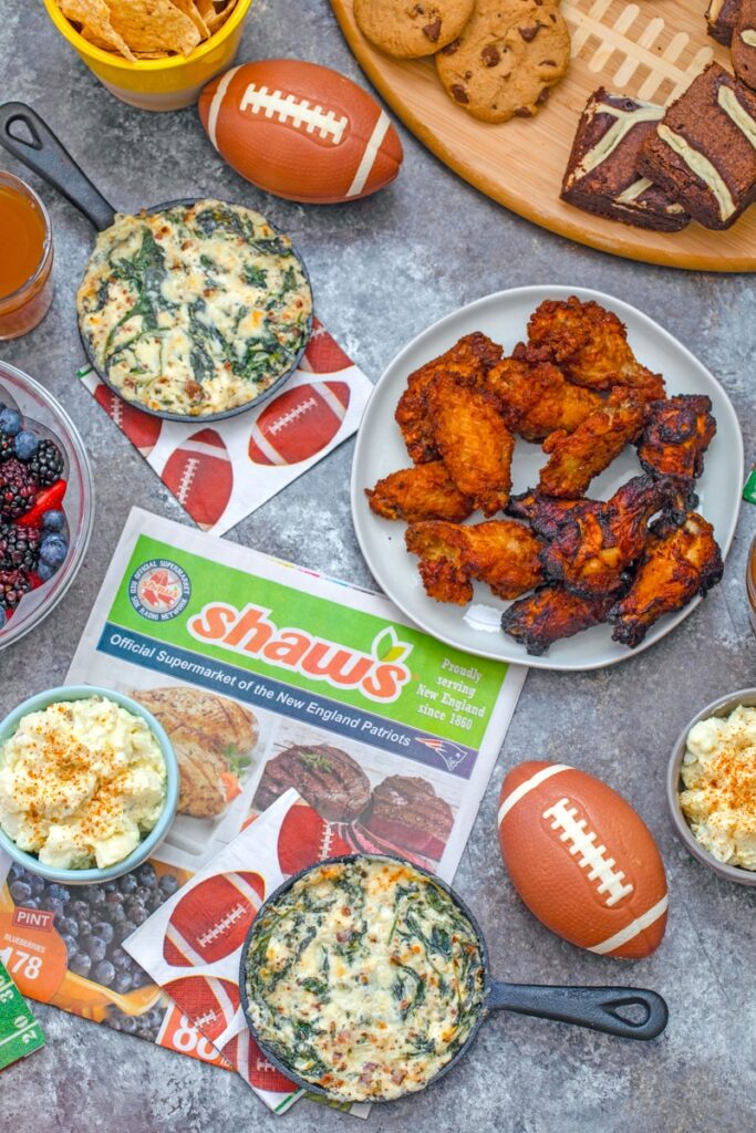 Overhead view of game day spread with dips, potato salad, chicken wings, and cookies and brownies with mini footballs and Shaw's circular