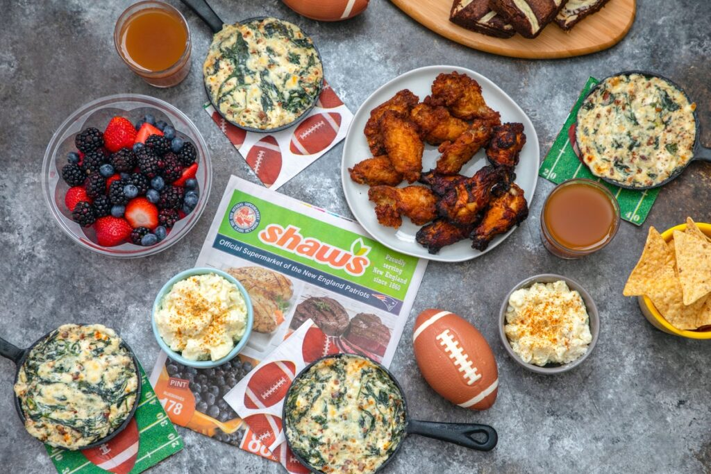 Landscape view of game day spread featuring dip, chicken wings, mixed berries, potato salad, tortilla chips, and mini football