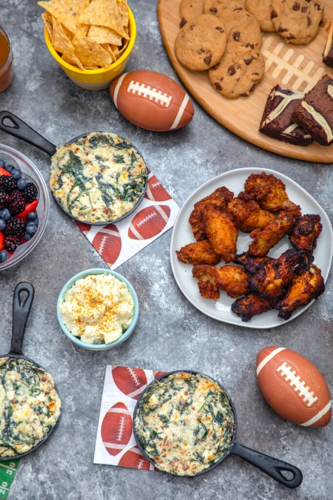 Overhead view of game day spread with dips, potato salad, chicken wings, and cookies and brownies with mini footballs