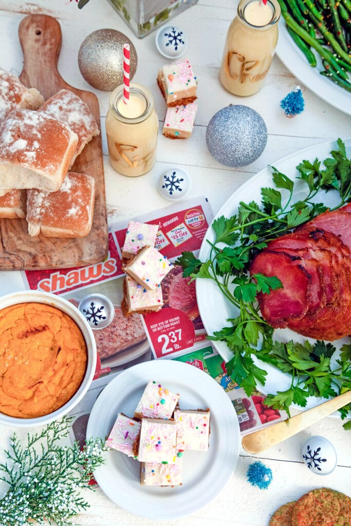 Overhead view of holiday dinner scene featuring ham, rolls, green beans, sweet potatoes, and cookie dough bars