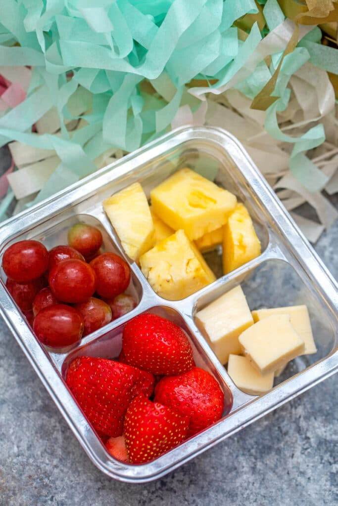 Overhead view of a snack pack featuring strawberries, grapes, pineapple, and cheese