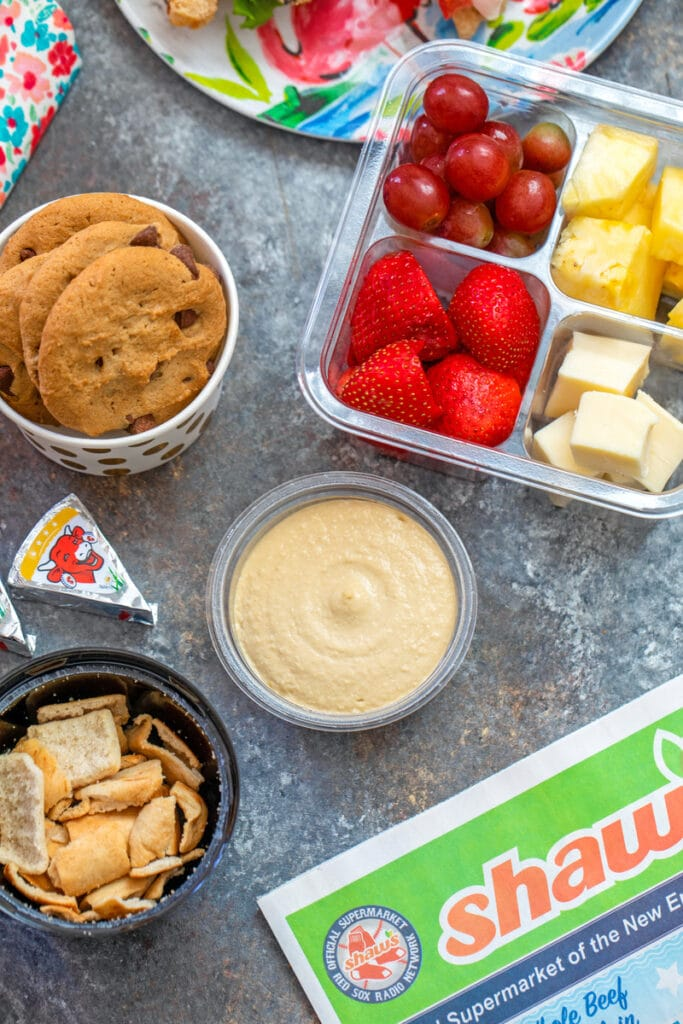 Overhead view of easy back-to-school snacks with hummus, pita chips, fruit, cheese, cookies, etc.