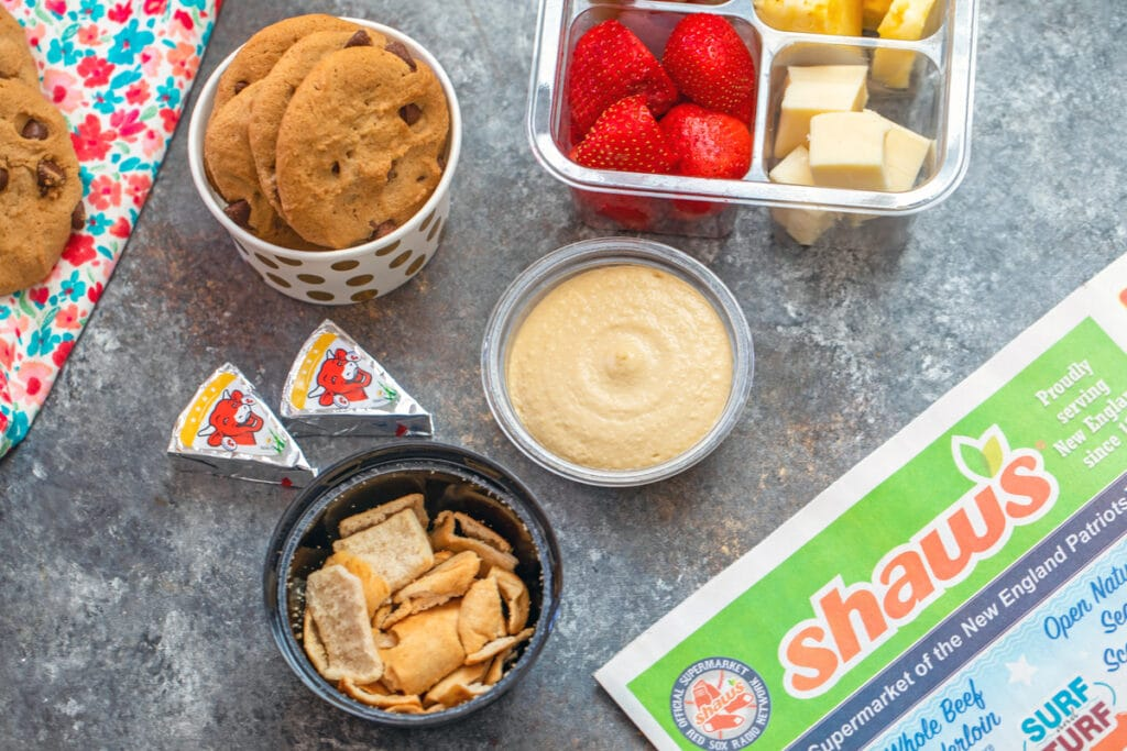 Landscape view of school lunch snacks like hummus, pita chips, cheese, fruit, and cookies