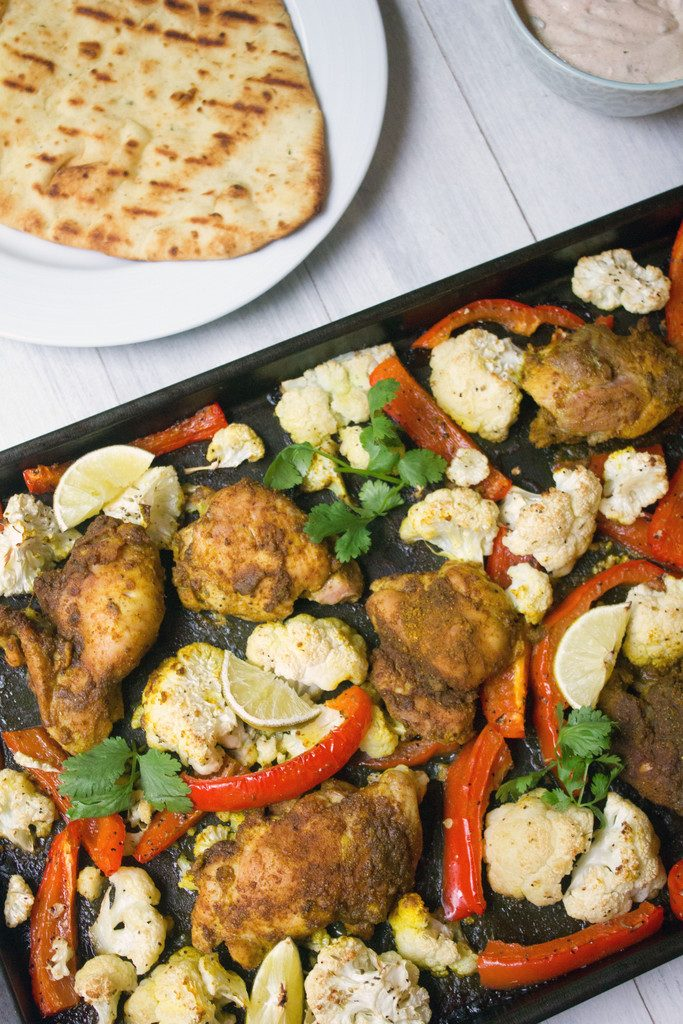 Sheet Pan Curry Chicken Thighs -- a sheet pan dinner with cauliflower and peppers, served with naan and yogurt sauce! | wearenotmartha.com