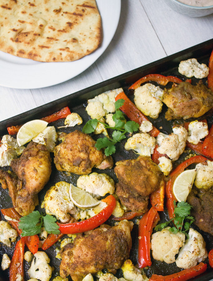 Sheet Pan Curry Chicken Thighs -- a sheet pan dinner with cauliflower and peppers, served with naan and yogurt sauce! | wearenotmartha.com