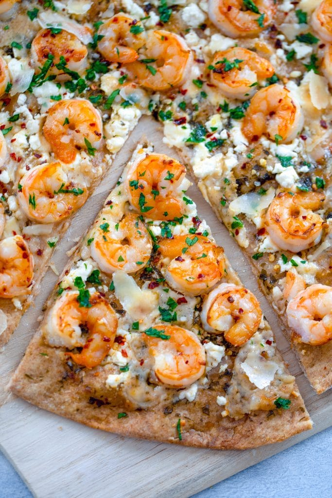 Overhead view of shrimp scampi pizza on wooden board with a slice pulled out