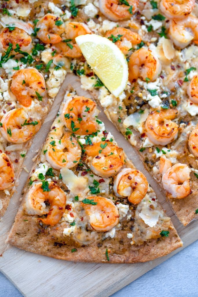 Overhead view of shrimp scampi pizza with a lemon in the center and a sliced pulled out on top of a wooden board