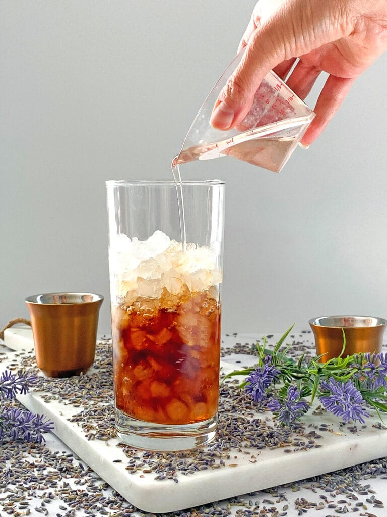 Lavender simple syrup being poured into coffee in ice-filled glass