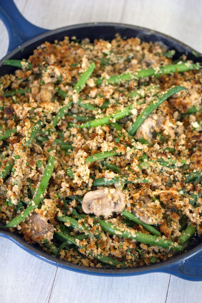 Close-up overhead view of skillet green beans with mushrooms and breadcrumb topping in a blue skillet