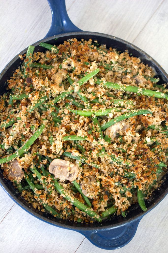 Overhead view of healthy skillet green bean casserole with mushrooms and breadcrumb topping in a blue skillet on white surface