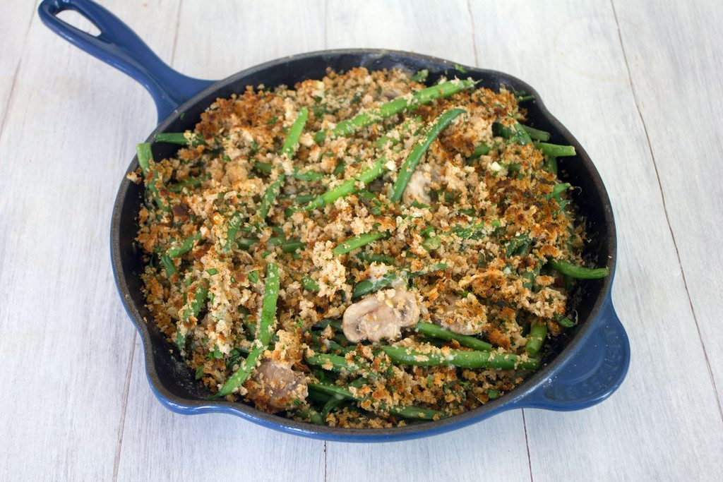 Landscape view of skillet green bean casserole topped with mushrooms and breadcrumb topping in a blue skillet on white surface