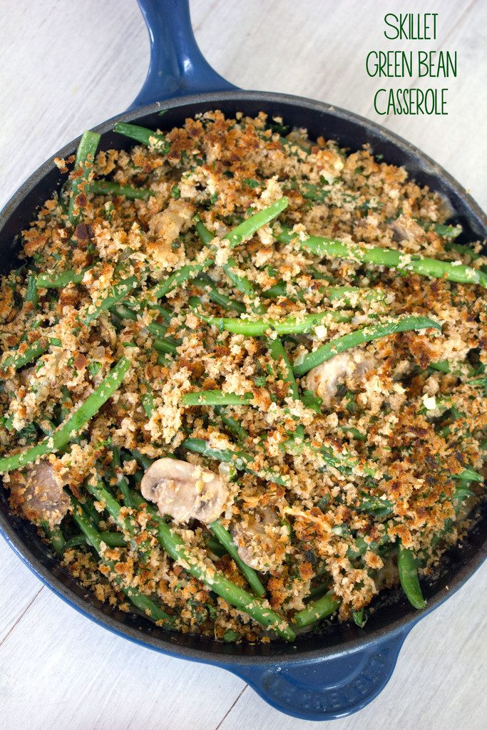 Overhead view of healthy skillet green bean casserole with mushrooms and breadcrumb topping in a blue skillet on white surface with recipe title at top of image
