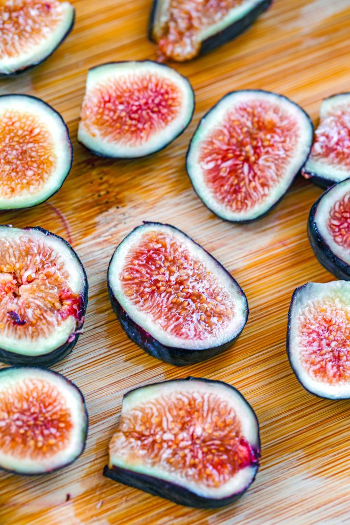 Overhead view of sliced figs on a cutting board