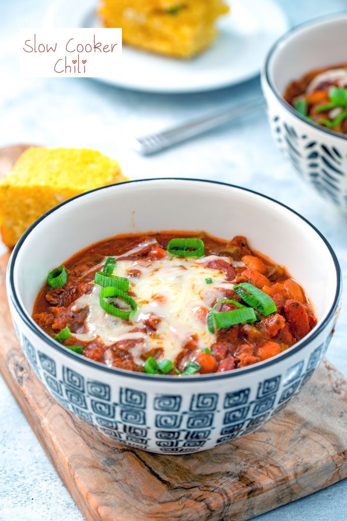 Head-on view of a black and white bowl of slow cooker chili topped with cheese and scallions with second bowl of chili and cornbread in the background with recipe title at top