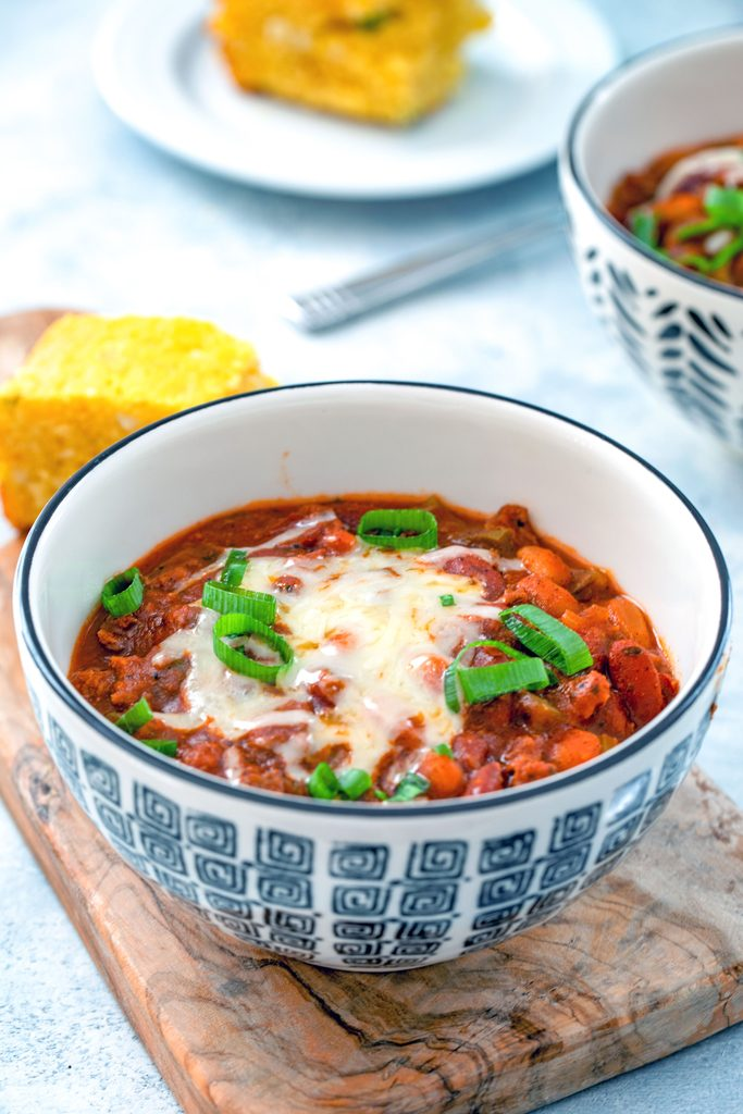 Head-on view of a black and white bowl of slow cooker chili topped with cheese and scallions with second bowl of chili and cornbread in the background