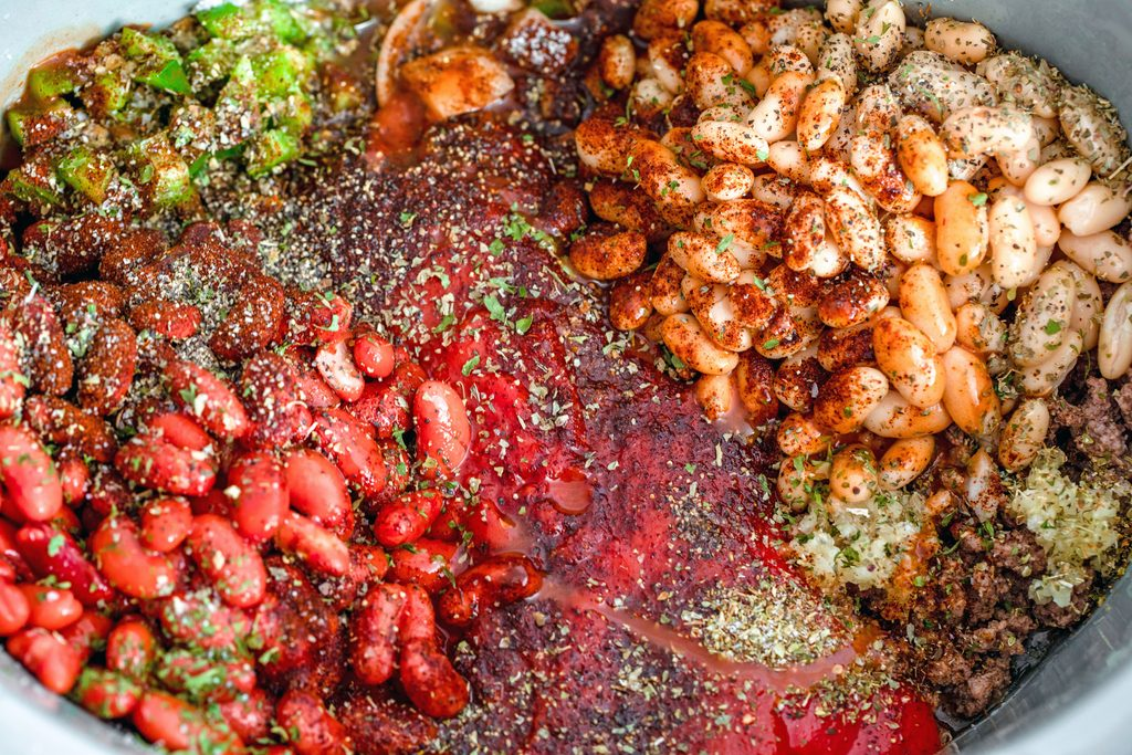 Overhead view of chili ingredients, including beans, tomatoes, beef, garlic, and peppers all in slow cooker