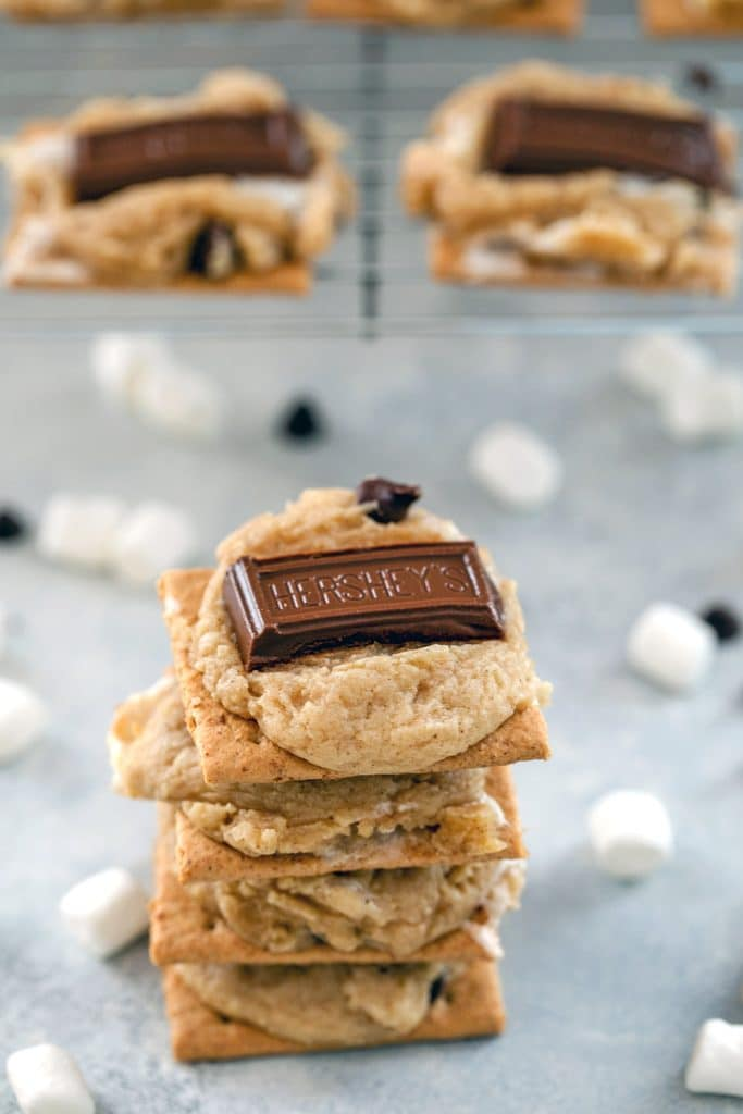 "Stack of four s'mores cookie bars surrounded by marshmallows and mini chocolate chips, with a baking rack with more cookies in the background and ""S'mores Cookie Bars"" text at top"