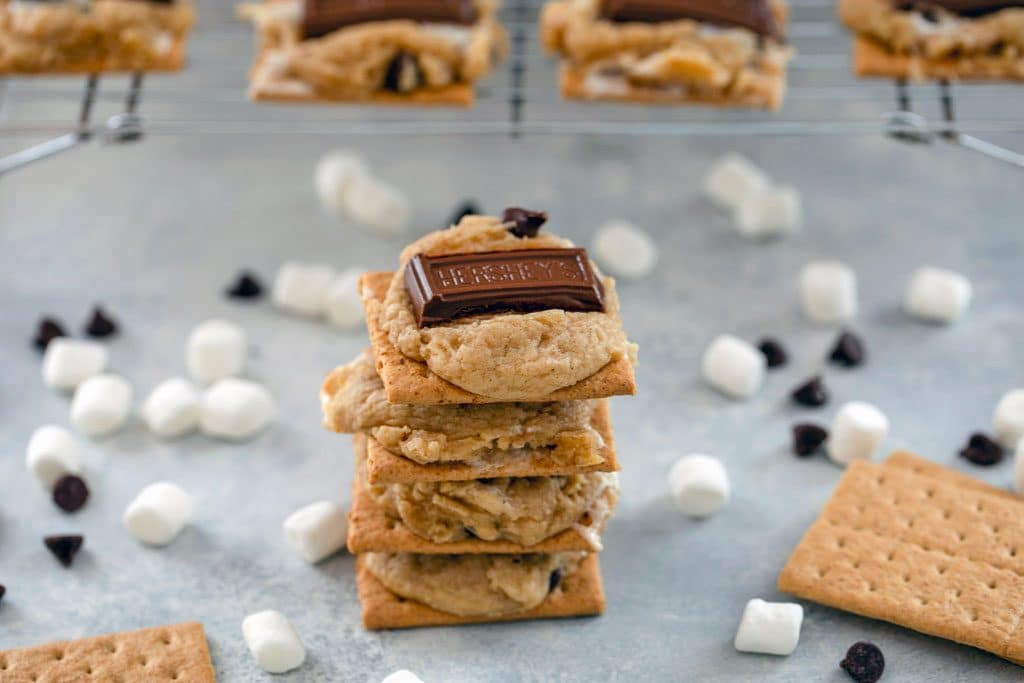 Landscape photo of stack of 4 s'mores cookie bars surrounded by mini marshmallows, chocolate chips, and graham crackers, with baking rack with more cookies in background